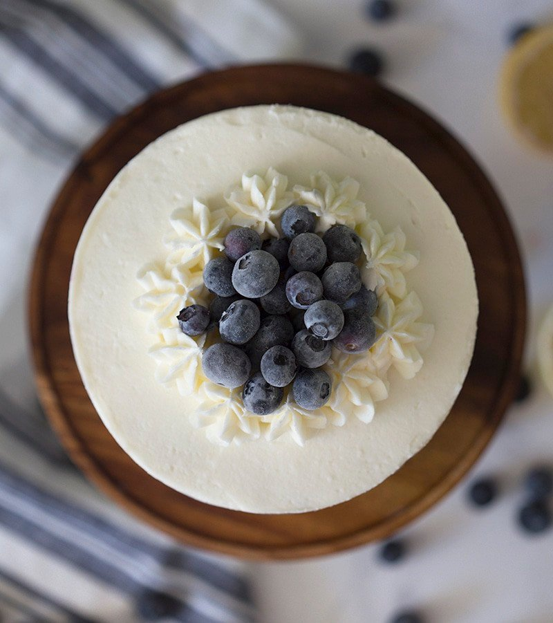 A top down shot of a blueberry lemon cake on a wooden cake stand