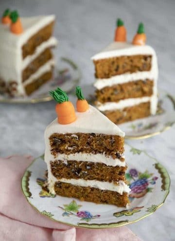 Pieces of three layer carrot cake on porcelain plates.