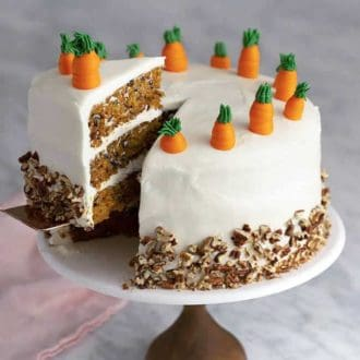 A three layer carrot cake on a cake stand with a piece being removed.