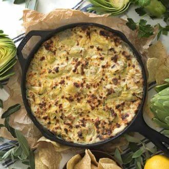 A skilled filled with baked artichoke dip.