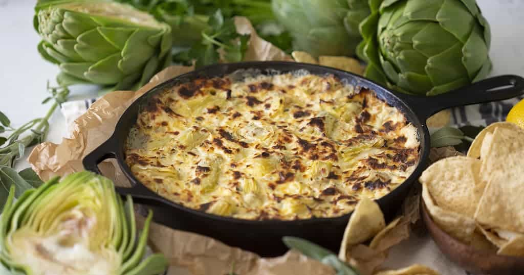 baked spinach dip in a skillet next to fresh artichokes and sage.