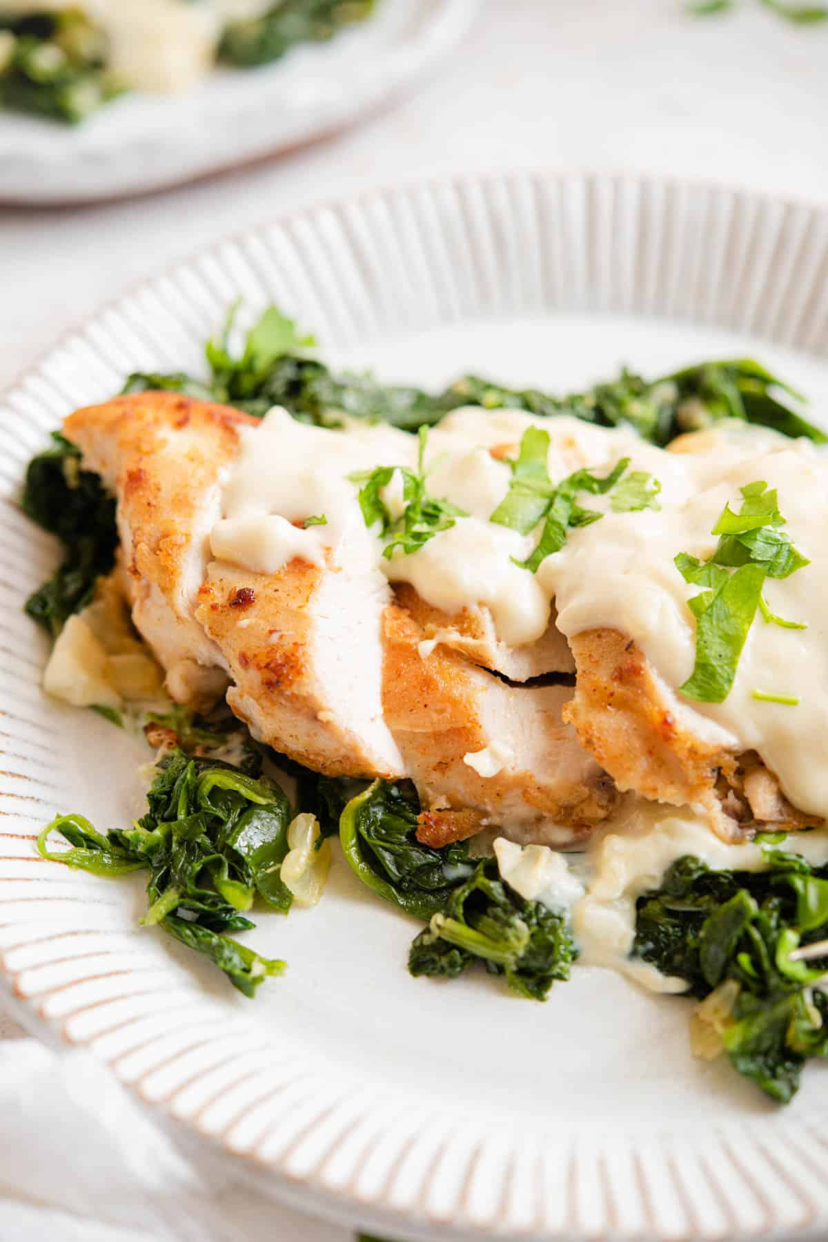 A close up of chicken cut into slices with spinach and cheese sauce on top