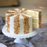 photo showing a striped coconut cake on a white cake stand