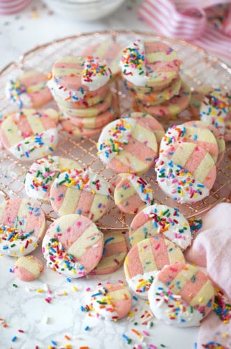 A photo showing pink and white striped funfetti cookies on a marble table.