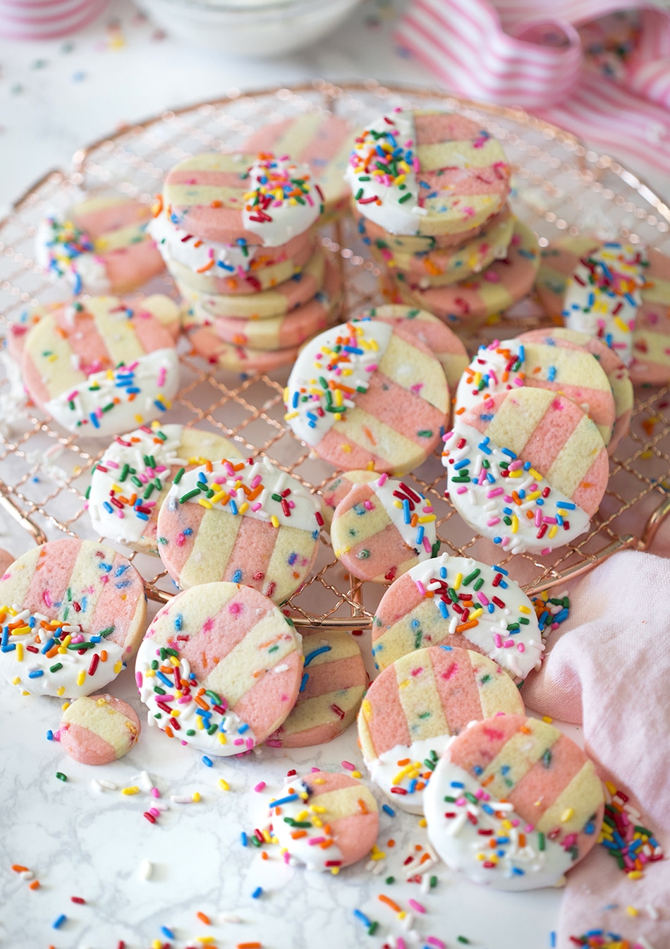 Photo showing pink and white striped funfetti cookies on a marble table.