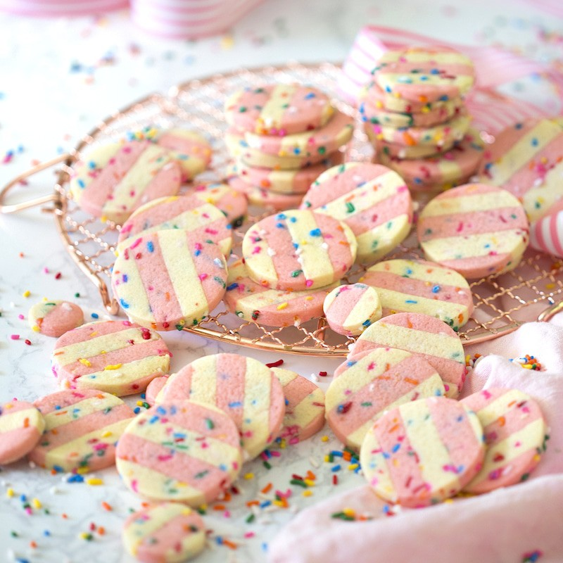 photo of pink and white funfetti cookies on a table before being dipped in white candy melt