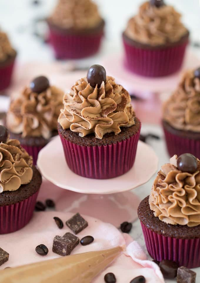 Mocha Cupcakes with chocolate and coffee beans around them.