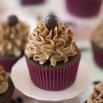 A mocha cupcake on a mini cake plate.
