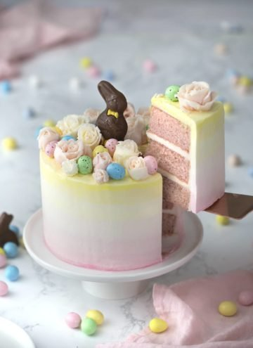 A photo of an Easter bunny cake with buttercream flowers, chocolate eggs and a chocolate Easter bunny on top.