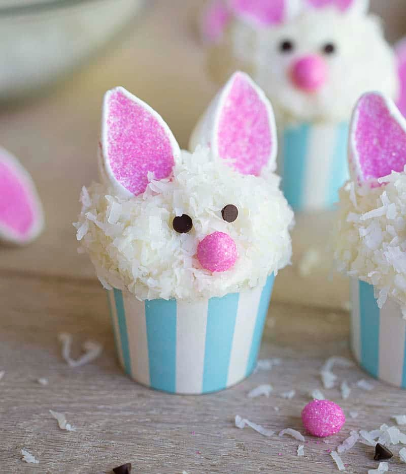 Easter bunny cupcakes on a wooden table.