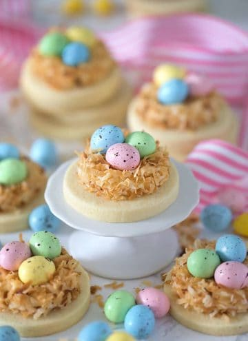 round sugar cookies topped with nests made with toasted coconut and candy eggs