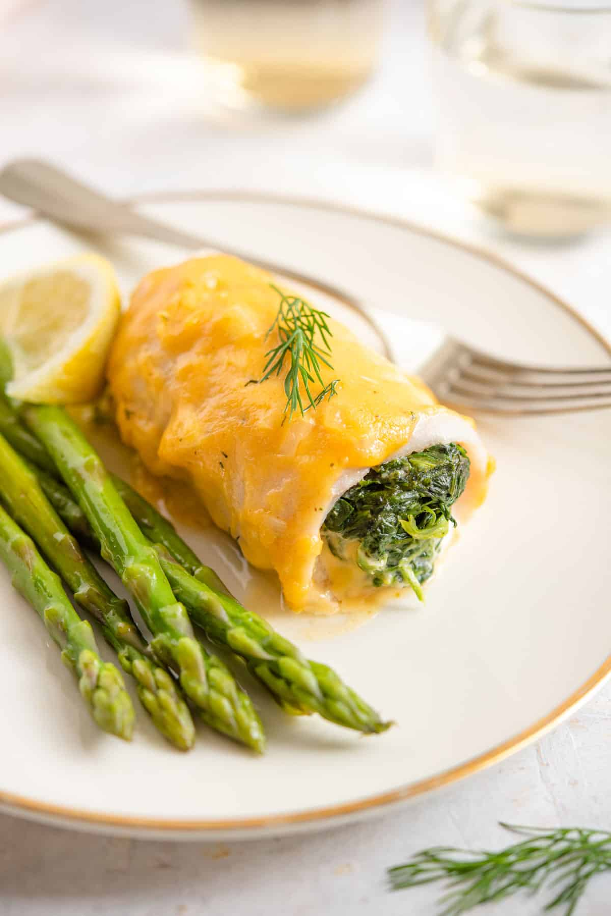 A close up of stuffed fillet of sole with a cheese sauce on a plate