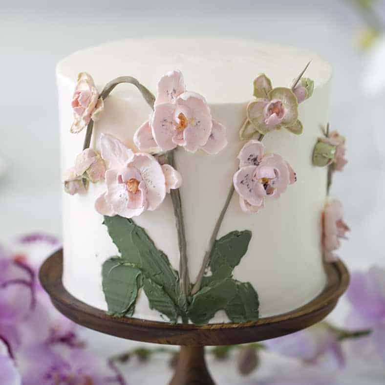 A photo of a cake covered in buttercream Orchids