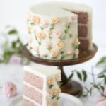 Photo of a strawberry cake on a wooden cake stand covered in buttercream roses with a piece out