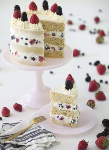 Photo of a Berry Cake cake on a pink cake stand with a piece on a plate