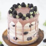 A photo of a blackberry cake with a soft purple blackberry drizzle and a crown of fresh blackberries.