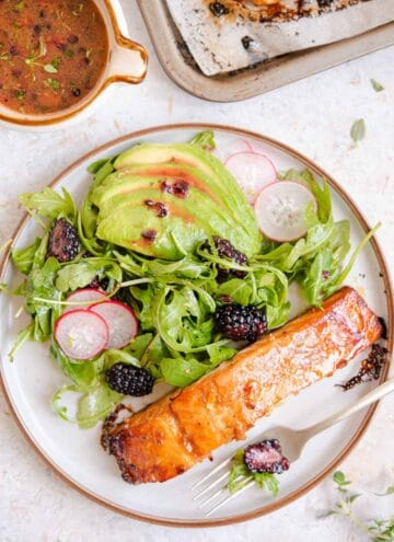 An overhead shot of glazed salmon on a plate with salad
