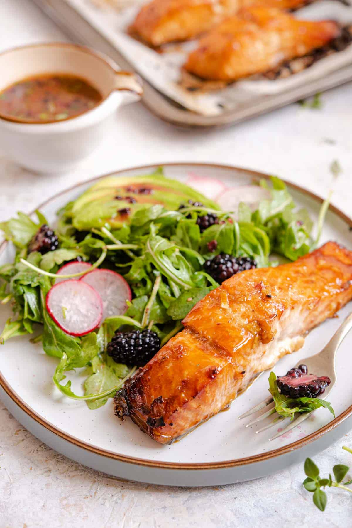 A side shot of glazed salmon on a modern plate with a blackberry salad