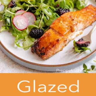 A side shot of glazed salmon and salad with glazed salmon written in text underneath