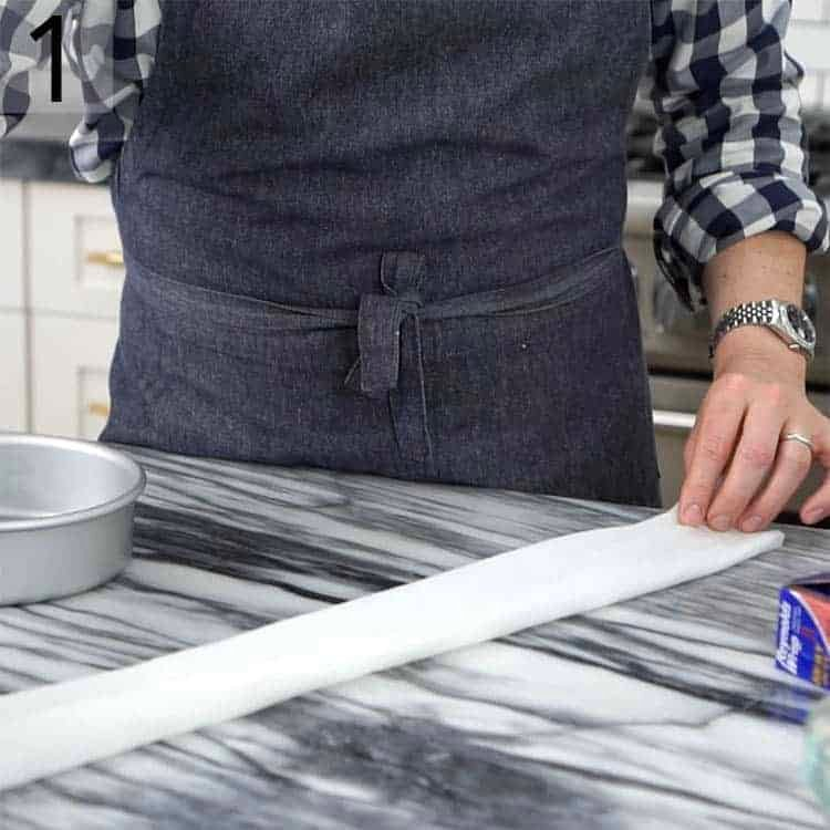 Paper towels getting folded to make homemade cake strips.