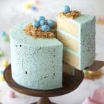 Photo of a blue vanilla cake with chocolate eggs on top.