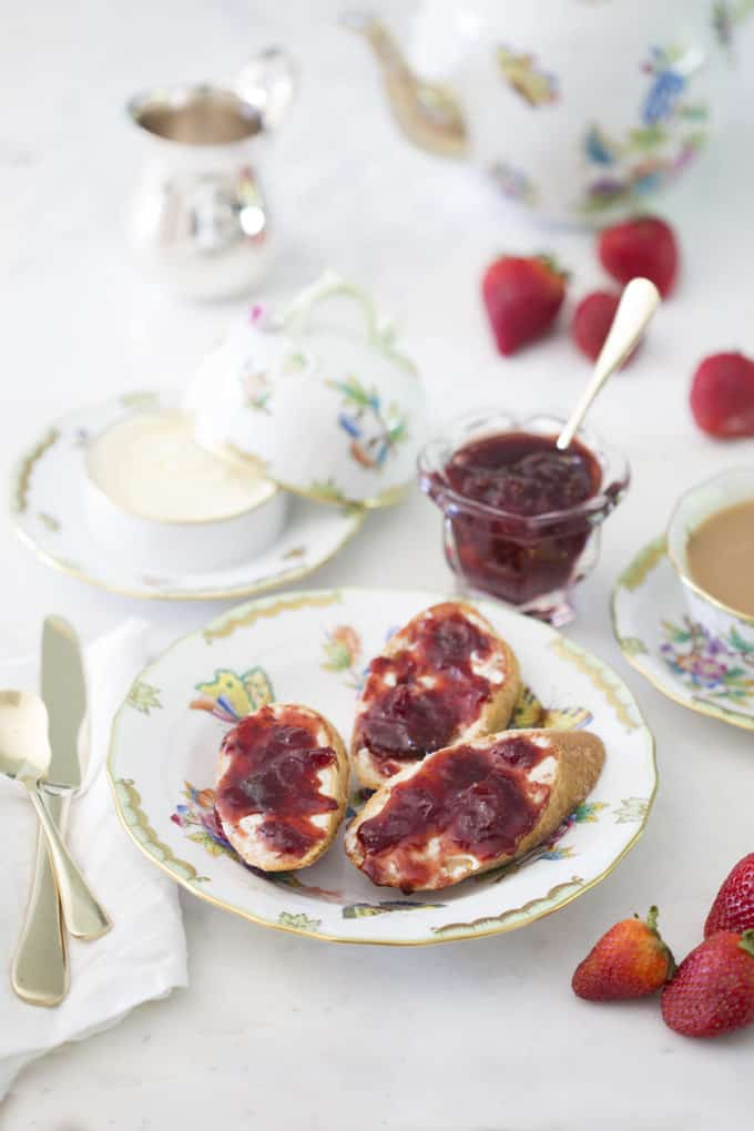 A photo of freshly made strawberry jam on french bread with butter.