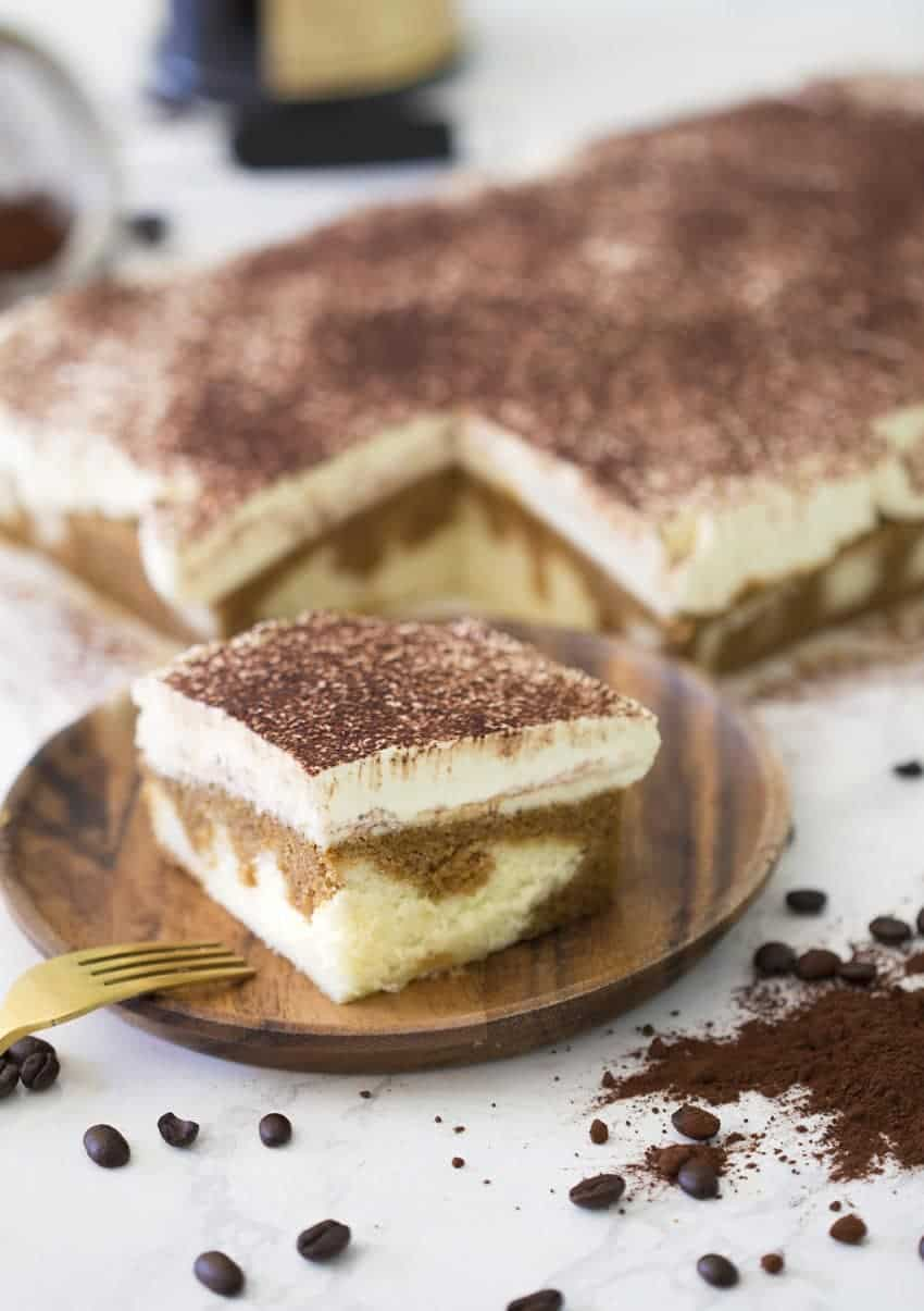 Photo of Tiramisu sheet cake with a piece removed and plated in the foreground
