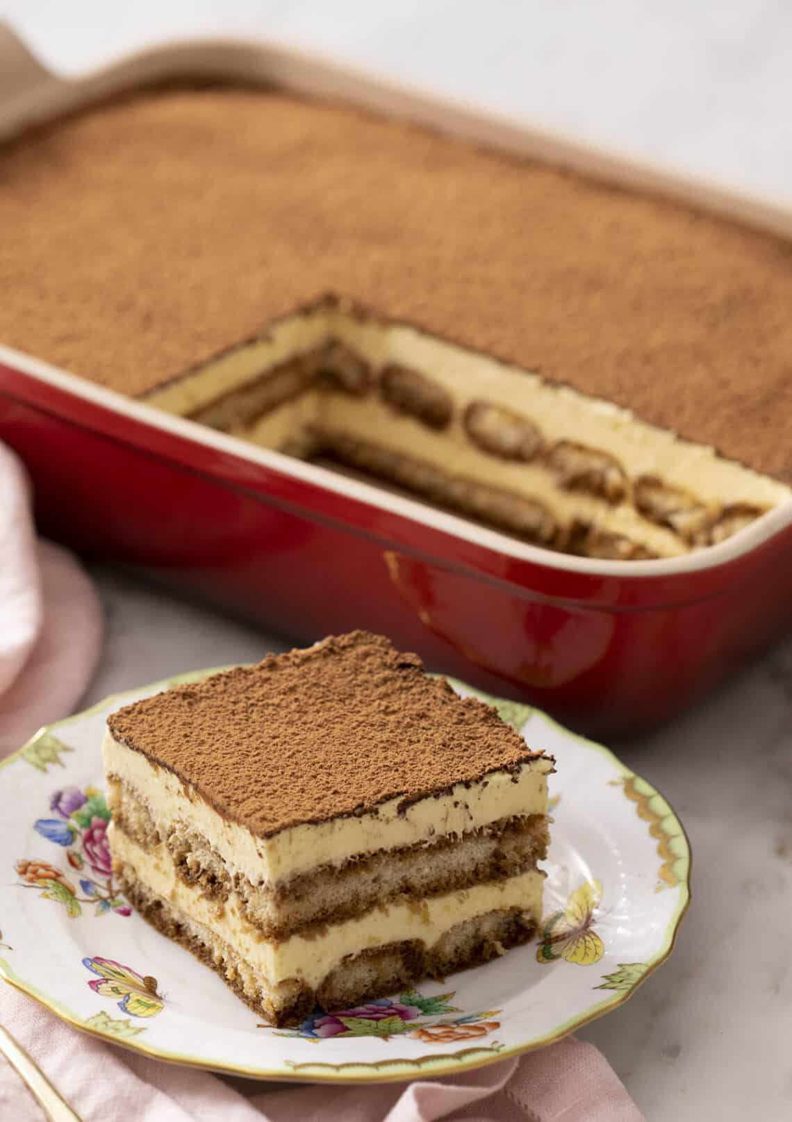 A piece of tiramisu in front of a red serving dish.