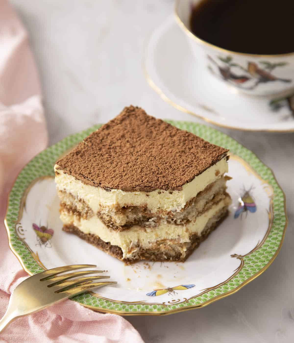 A piece of tiramisu with a bite taken out next to a cup of coffee.