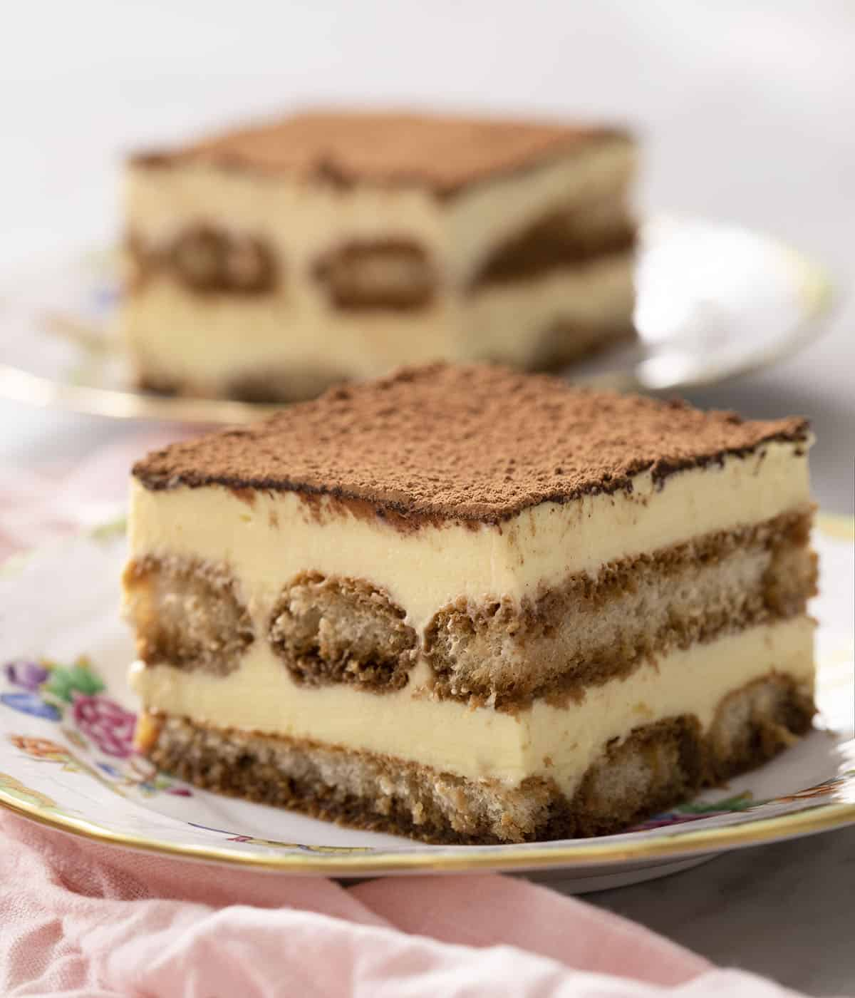 Two pieces of tiramisu filled with ladyfingers soaked in espresso.