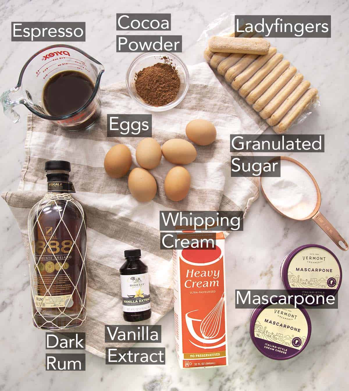 The ingredients needed to make tiramisu on a marble counter.