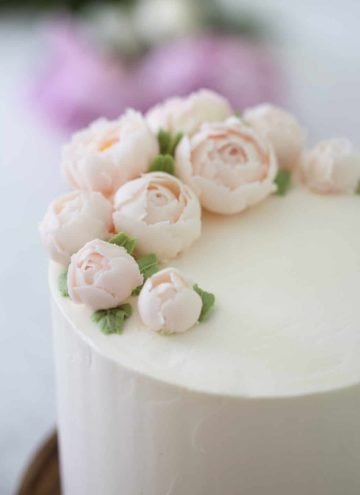 Close up 3/4 view of a lemon elderflower cake topped with soft pink buttercream peonies