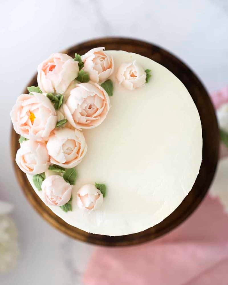 Top Down view of a lemon elderflower cake with soft pink buttercream peonies