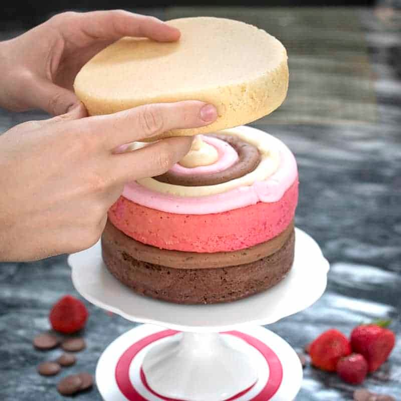 Photo of a Neapolitan cake being assembled on a white cake stand.
