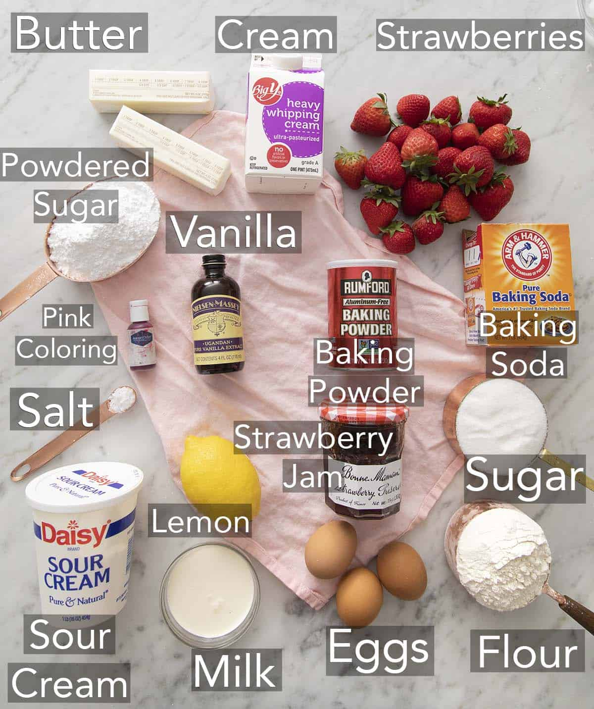 Ingredients for making strawberry cupcakes on a counter.