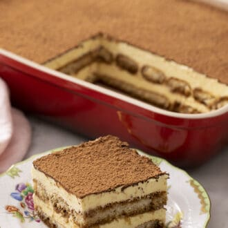 A piece of tiramisu in front of a dish of it.