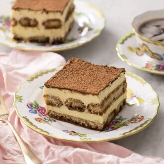 Two pieces of tiramisu next to a cup of coffee.