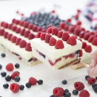Photo of an American flag berry cake with a piece being removed.