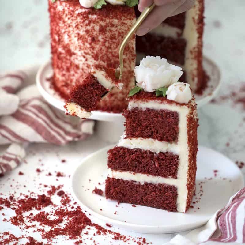 Photo of a piece of red velvet cake being eaten