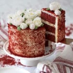 photo of Red Velvet Cake covered in buttercream roses on a white cake stand with a piece being removed