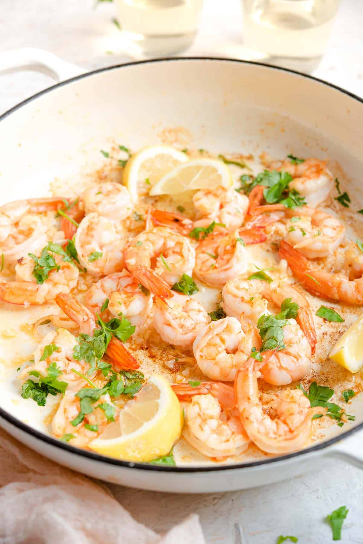 A side shot of cooked shrimp in a pan with lemon wedges and parsley