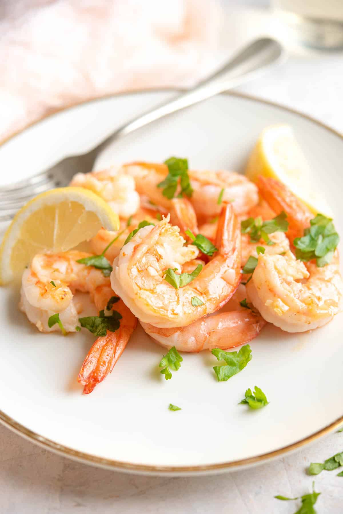 A side shot of sauteed shrimp on a plate with parsley