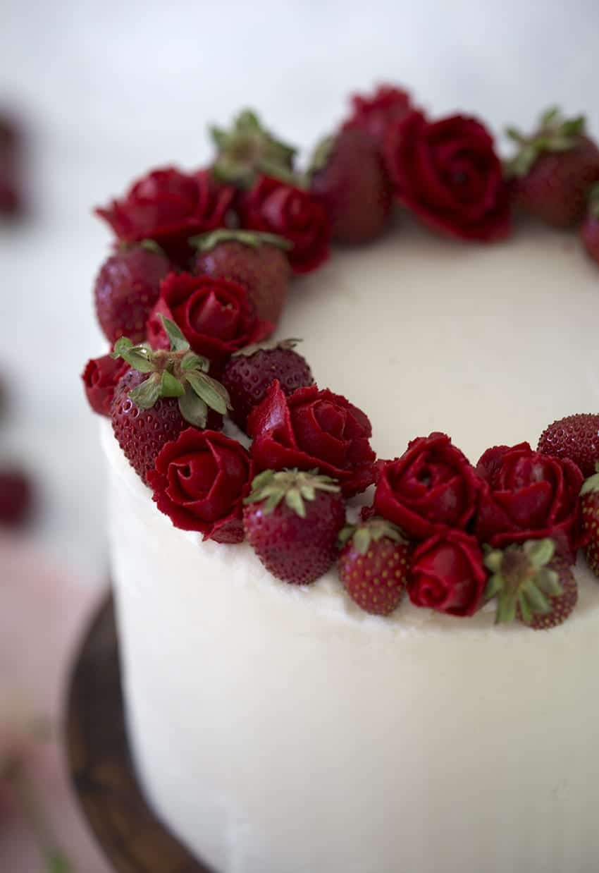 A close-up photo of a Strawberry cake with strawberries and red buttercream roses on top