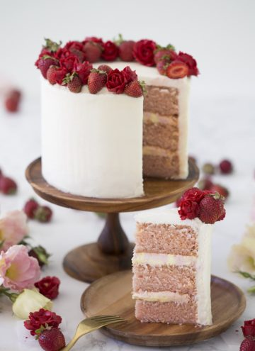 Photo of a pink Strawberry cake with a piece removed on a wooden plate.
