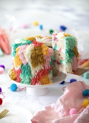 Photo of a colorful cake shag on a white cake stand with a piece being removed