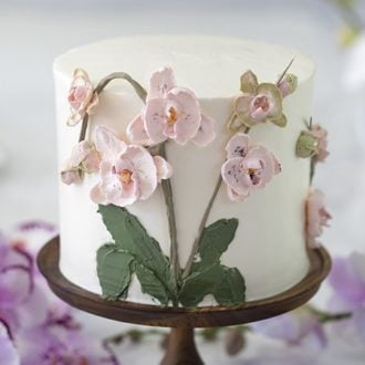 photo of a brown butter cake covered in buttercream orchids