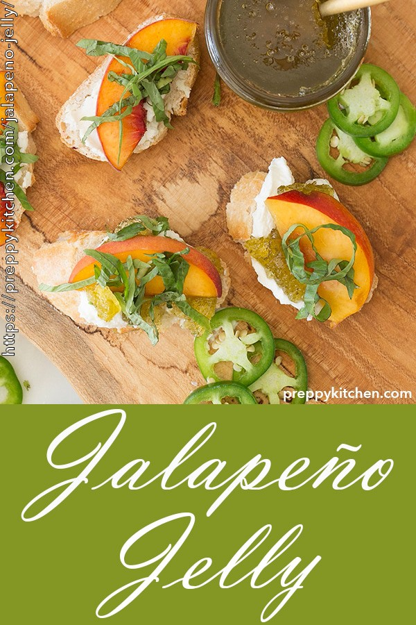 A clipping of jalapeno jelly on toasted bread, topped with goat cheese, a piece of a sliced peach and basil.