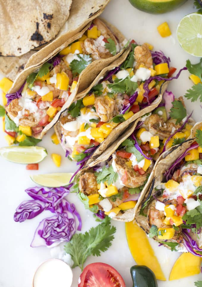 A photo of shrimp tacos topped with mango salsa, cabbage, cilantro and lime, taken from above.