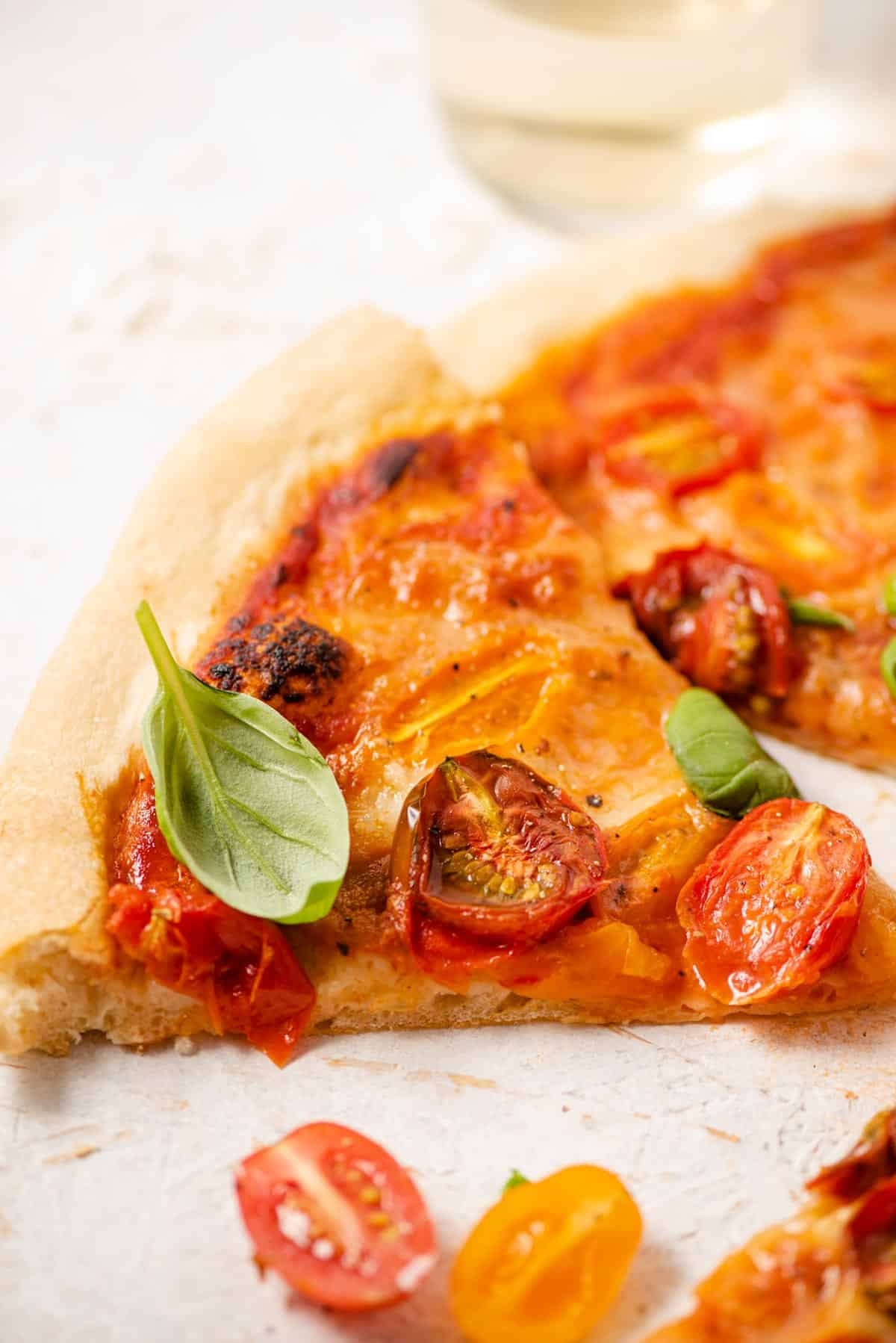 A close up of one slice of tomato pizza topped with fresh basil