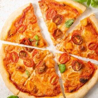 A square image of a tomato pizza cut into slices
